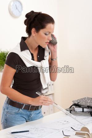 young female architect holding telephone