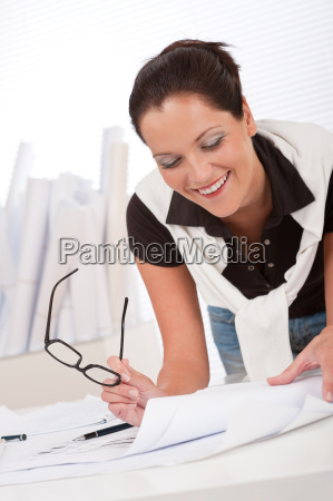 young female architect with plans at