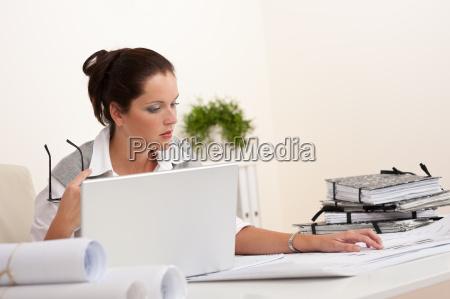 female architect with laptop sitting