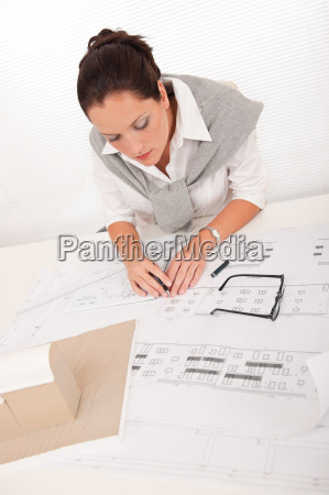 attractive female architect watching plans