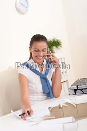 female architect with phone sitting at