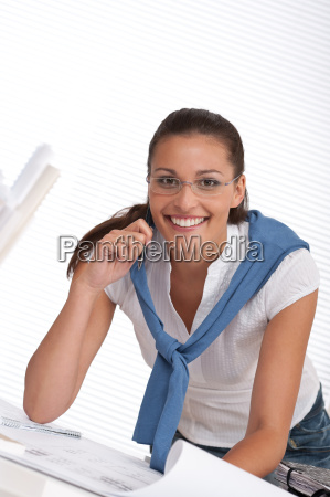 happy female architect with plans at