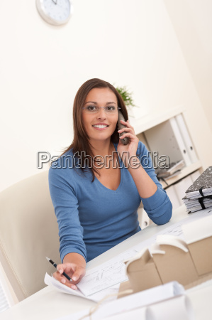 smiling female architect holding phone and