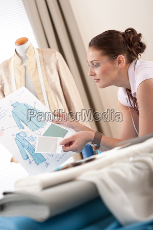 professional tailor holding fashion sketch