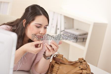 young executive woman applying lipstick at