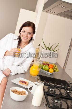 young woman having breakfast in modern