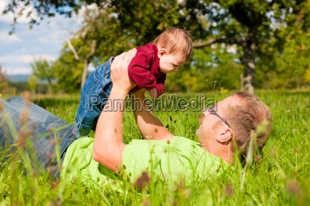 father plays with baby on meadow