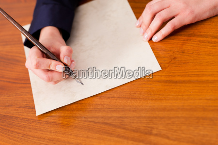woman writes a letter with pen