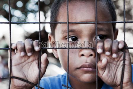 asian boy against fence focus