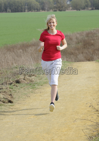 young woman jogging on a dirt