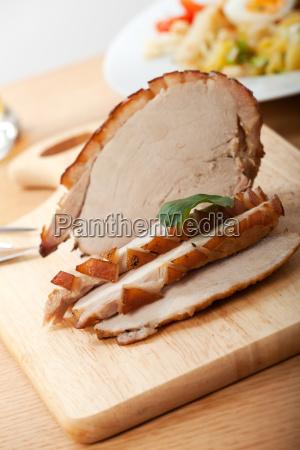 schweinebraten wird in scheiben geschnitten