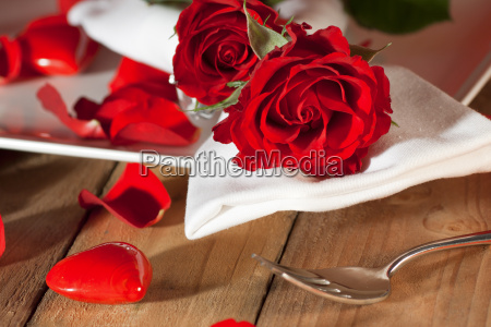 place setting with red roses in