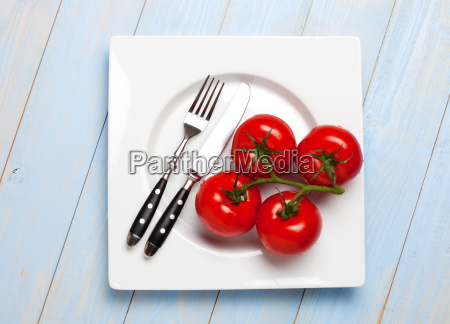 four tomatoes on a white plate