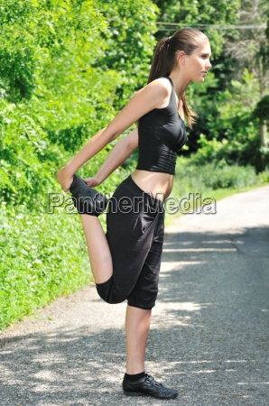 woman performs stretching before running