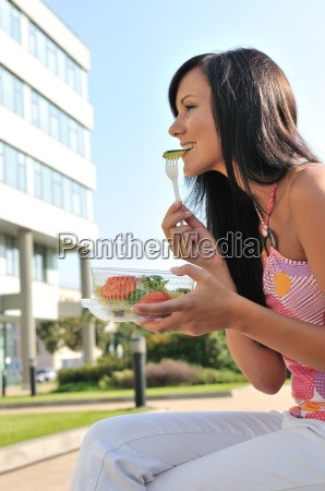 young woman eating salad outdoors
