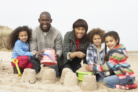 young family building sandcastle on beach