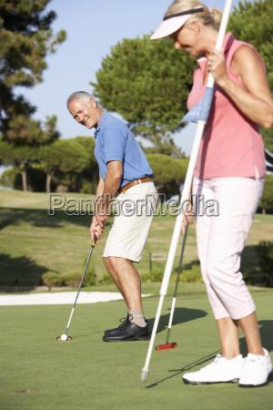 senior couple golfing on golf course