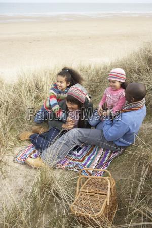 family sitting in dunes enjoying picnic
