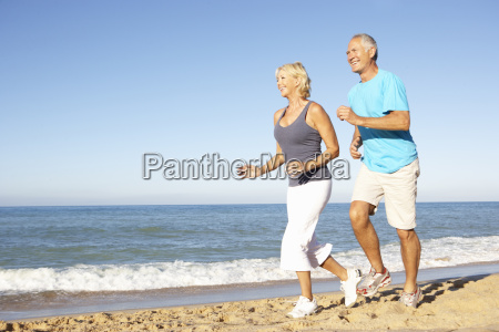 senior couple in fitness clothing running