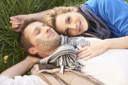 young couple lying together on grass