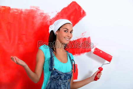 young woman painting house wall in