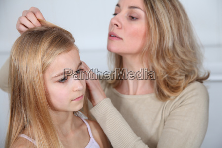 mother treating daughters hair against lice