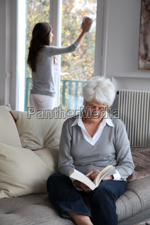 elderly woman reading book while housekeeper