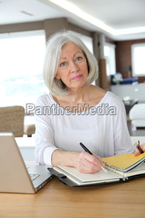 senior woman at home writing on