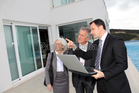 senior couple visiting luxury villa with