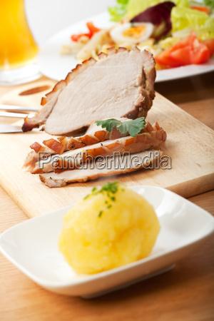 schweinebraten in scheiben und kartoffelknoedel