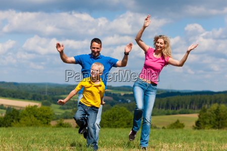 family playing catch on the meadow