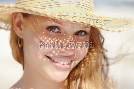 woman in straw hat smiling at
