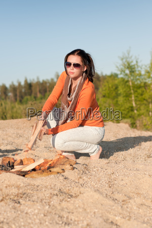 camping happy woman making campfire on