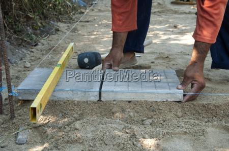 worker puts sidewalk tiles