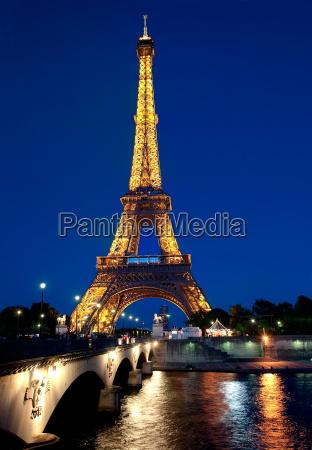 eiffel tower illuminated at dusk