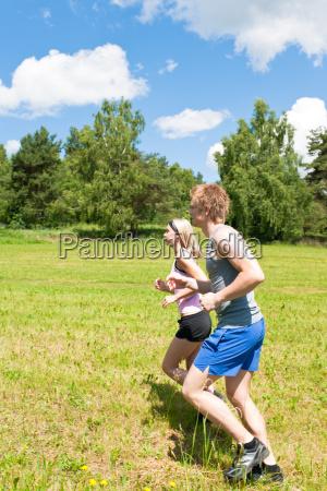 sportive young couple jogging meadows sunny