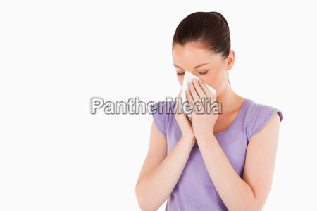 good looking woman sneezing while standing