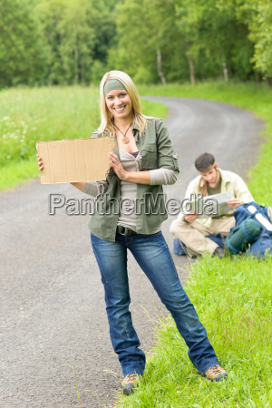 hitch hiking young couple backpack asphalt