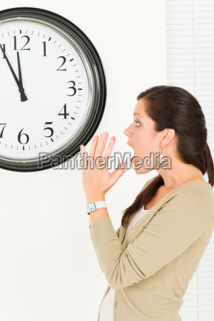 surprised punctual businesswoman looking at clock