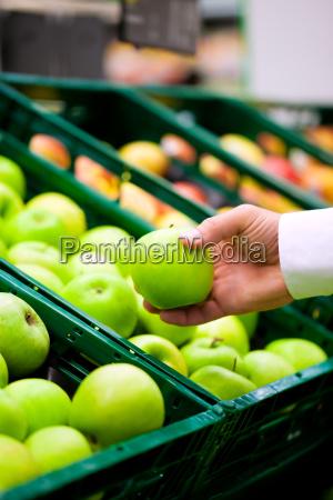 man in supermarket buying fruit