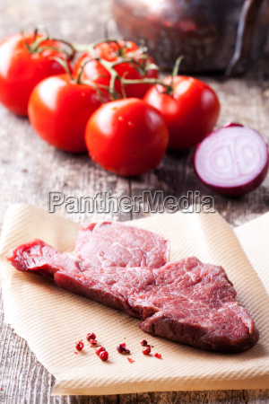 raw steak and peppercorns