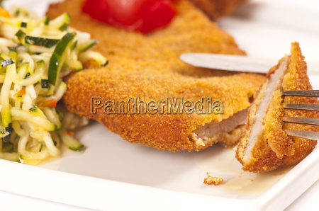 schnitzel with slices of tomato and
