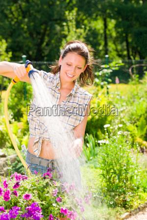 summer garden smiling woman watering hose