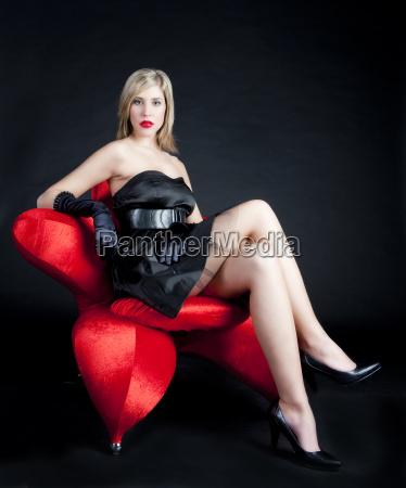 young woman wearing black dress sitting