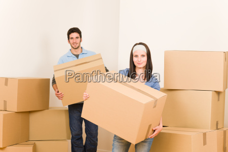 moving home young couple carrying cardboard
