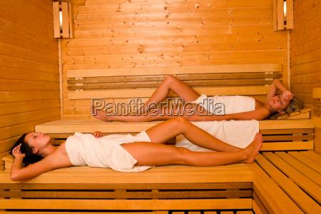 sauna two women relaxing lying wrapped