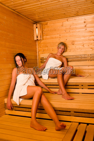sauna two women relaxing sitting wrapped