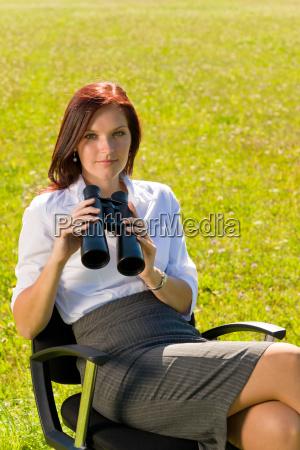 businesswoman sit in sunny meadow seek