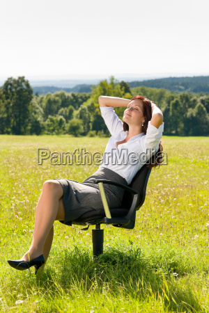 young businesswoman sunny meadow relax on