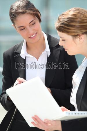 zwei weibliche kollegen arbeiten diskutieren